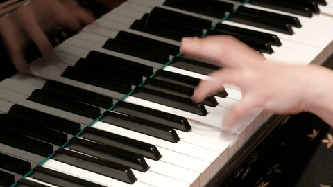 Piano playing. Close-up. Musical theme. Concert program. Female hands press piano keys.
