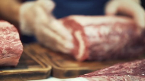 Close-up of butcher hands in white protective gloves preparing a large cut of meat for cooking or sale. Action. Butcher work