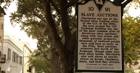 Charleston, South Carolina, USA – October 23, 2018: Historical marker describing the slave auctions and trading in the 1800s around the Old Exchange Building in Charleston South Carolina USA