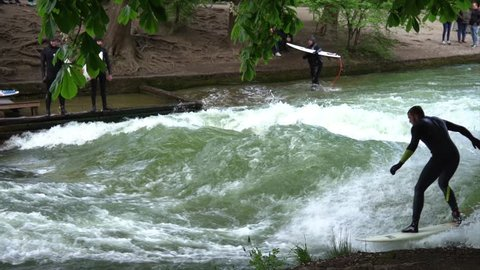 Munich/ Germany 07/05/2019: River surfing on Eisbach or Isar man made river in Munich Germany. Near the Haus der Kunst art museum, the river forms a standing wave about one meter high.