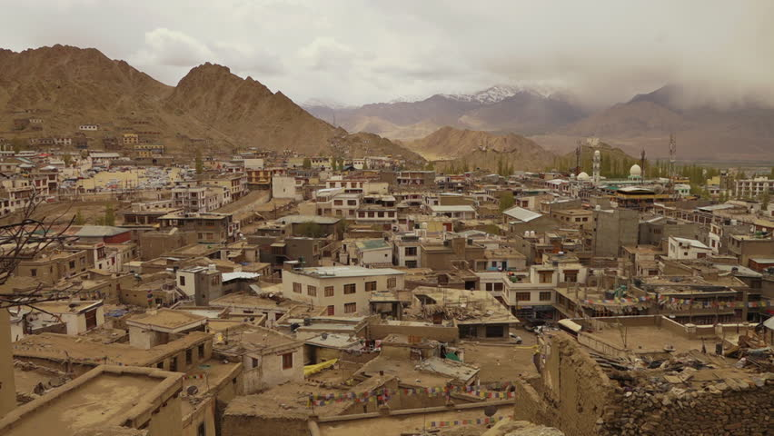 Wide, panning, high angle shot of Leh city capturing traditional Buddhist residential building architecture, stone ruins of Leh Palace, monastery on a hill top, temples, pine trees, and surrounding