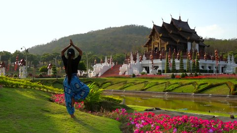 Young woman in traditional asian clothes relaxing by practicing yoga on background Thailand temple and nature landscape. Slow motion.