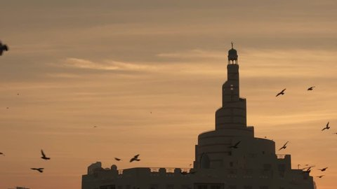 Early morning sunrise with birds flying and mosque in the background, Doha, Qatar.