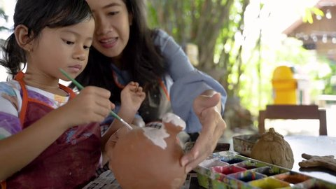 mother and daughter making ceramic pot in pottery workshop