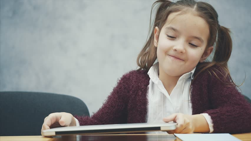 A schoolgirl is sitting at the table. While reading this book, he reads. Happy. | Shutterstock HD Video #1029247298