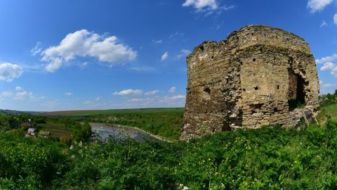 Timelapse of spring castle ancient ruin- wind moving white clouds at blue sky and green grass with old historical fortess ruins - Zvanets, Ukraine. On of the travel and tourism destination