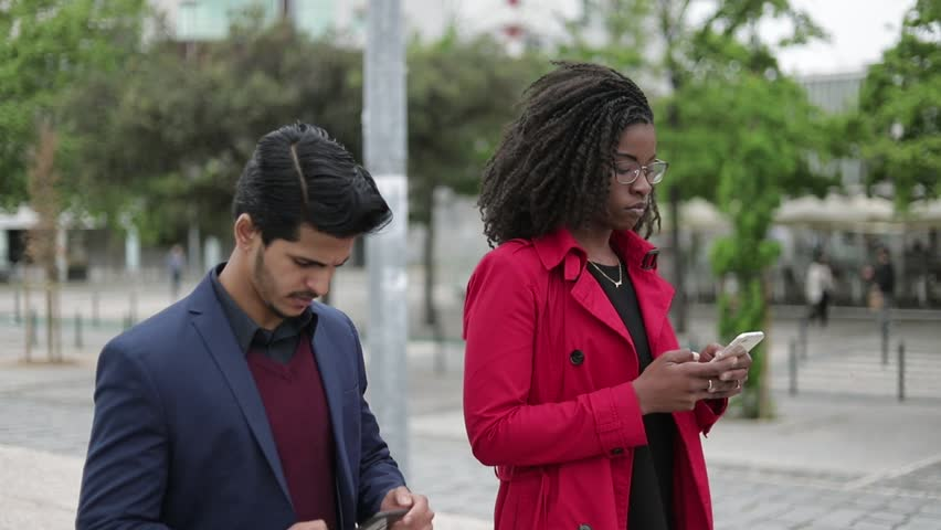 Side view of pretty Afro-american woman in spectacles and rose coat and handsome mixed-race man in navy blue suit walking along street, texting on phones. Communication, lifestyle concept | Shutterstock HD Video #1029318968