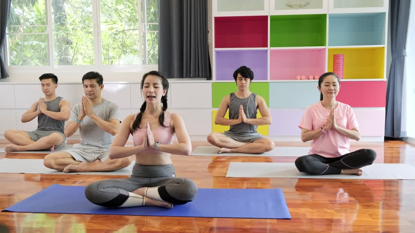 Group of young and senior asian people attending yoga class, sitting down raising arms. Group sport lifestyle. | Shutterstock HD Video #1029329648