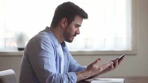 Angry annoyed young business man holding using texting on smartphone frustrated by stuck broken phone missed call bad service, stressed mad male customer outraged having problem complain on cellphone