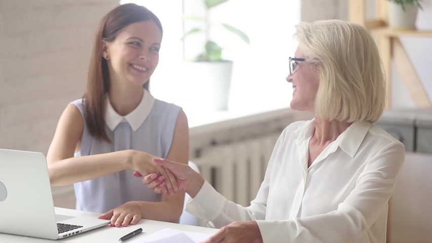 Aged and young businesswomen sit at desk in office shake hands, satisfied client read agreement check terms conditions handshake with manager, closing deal, finalize contract between buyer and agency