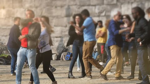 Brussels, Belgium - April 1, 2019:Funny view of smiling people dancing actively and turning around at a high stone wall on a sunny day in spring in slow motion