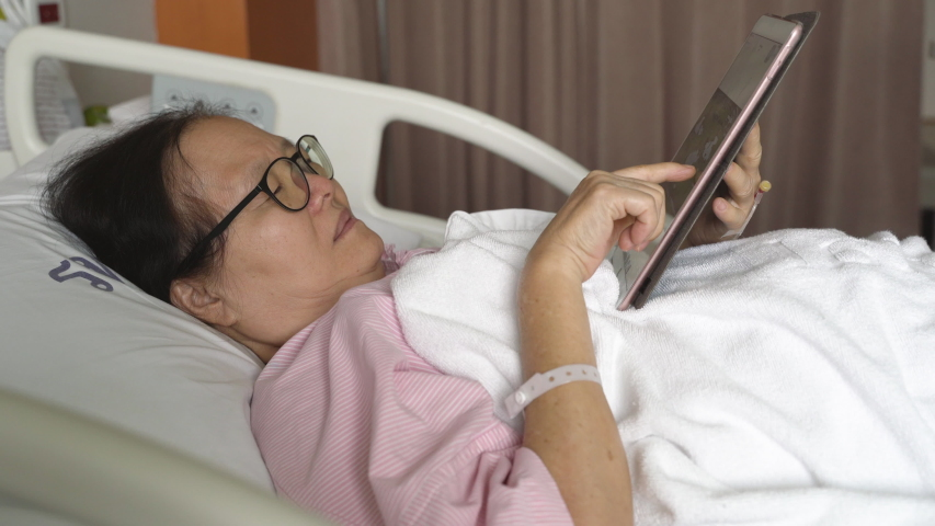 Elderly patient woman lying in hospital bed  and using digital tablet for relaxing