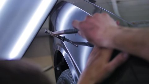 Paintless dent removal. Close up hammer with rubber and machine. Tools for leveling dents without painting. Male master repairs the car in the auto repair shop. Aluminum Hand Tool hammer