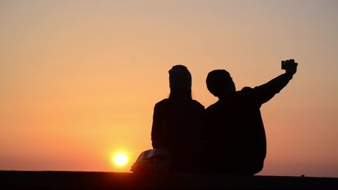Silhouette of romantic couple in love at sunset at the sea. Boy and girl enjoying at sunset and taking selfie with phones on holidays. Happy couple hugging and kissing at summer evening.