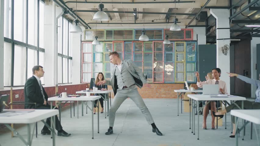A young businessman in a business suit enters the office, starts to dance expressively, grabs a glass from the employee's table and throws it. Coworking in loft style. Office life. Celebration | Shutterstock HD Video #1029418778