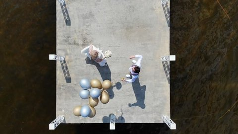 aerial video, top view, beautiful newlywed couple, bride and groom dancing outdoors, on a pier, groom holds balloons in his hand, summer sunny day. wedding