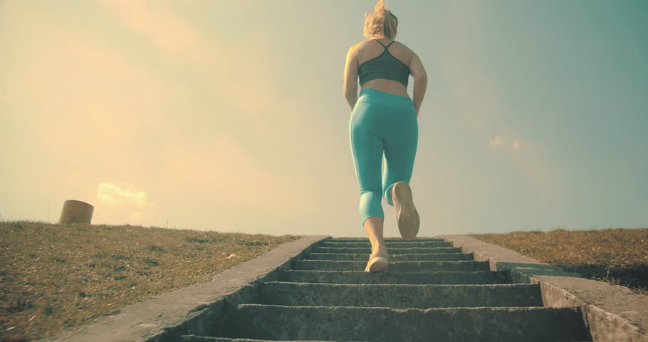 Runner 4K slow motion video. Woman running walking in outdoors park on sunny day, close-up legs sport shoes. Young woman doing sports workout. Female exercising in the gym fitness training.