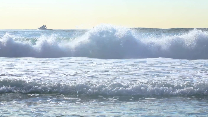 Blue turquoise waves with white was crashing onto the shoreline of a orange white sandy beach along the Gold Coast, Australia coastline at sunrise with blue orange skies and crystal clear blue water | Shutterstock HD Video #1029489188
