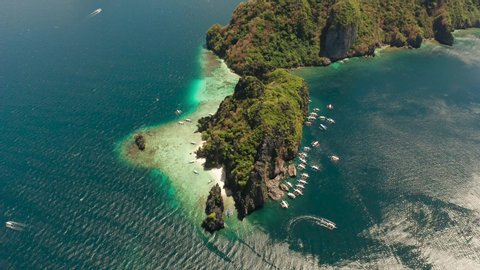 aerial view of tourist boats over tropical island with sandy beach and coral reef. El nido, Philippines, Palawan. tropical landscape bay with beach and clear blue water.