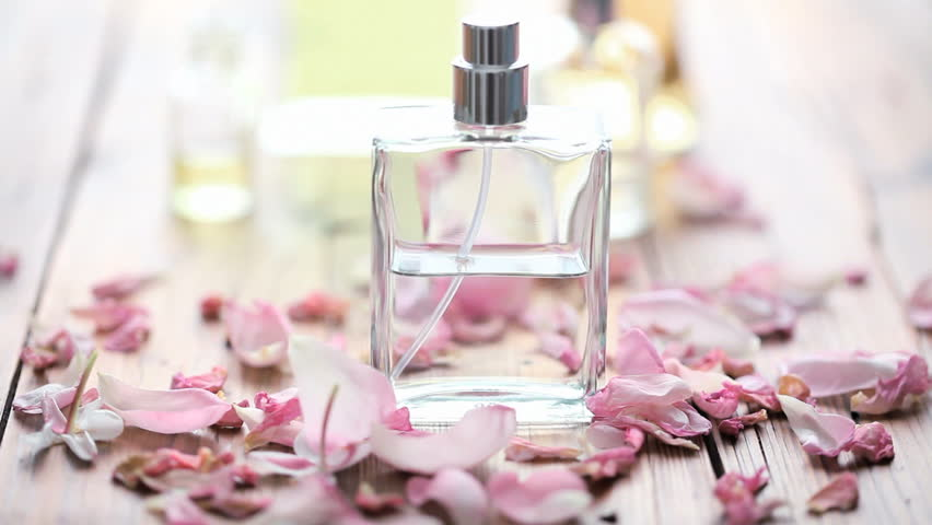 rose petals blown away from perfume bottle