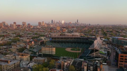 Chicago, Illinois / USA - May 13 2019: Fixed Wing Shot of Wrigley Field During Sunset with Chicago Skyline in Background - [4K]