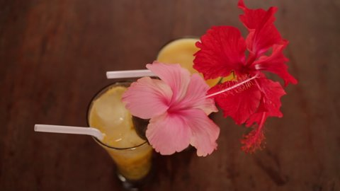 Hibiscus flowers decorate two fruit cocktails on wooden table