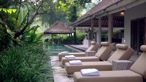 Row of lounging chairs on pool terraces in exotic hotel. Outside area with pool