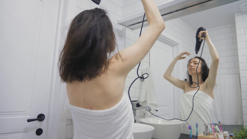 Young happy woman blow drying hair in bathroom, lifestyle. Hair style beauty concept.