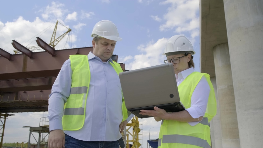 engineer man and foreman woman use laptop against background of reinforced concrete structure of overpass. #1029598238