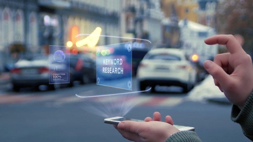 Female hands on the street interact with a HUD hologram with text Keyword research. Woman uses the holographic technology of the future in the smartphone screen on the background of city   Shutterstock HD Video #1029623168