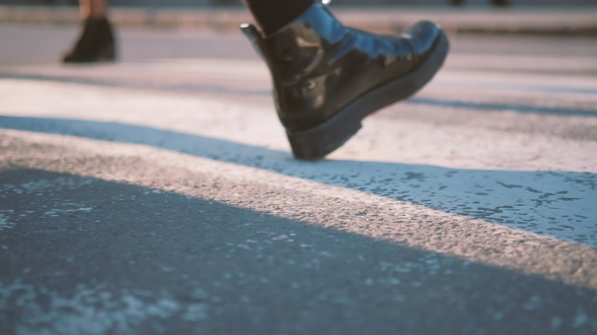Woman crossing city street on crosswalk. Black patent leather boots closeup. Smart urban lady hurrying along smooth road.