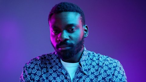 Portrait of handsome young African American male dressed in flowered shirt looking at camera with serious and confident expression on his face in neon lights. People and lifestyle concept. Male studio