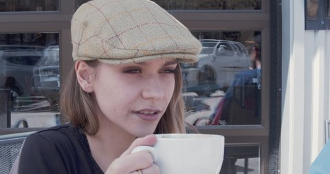 Young lady sips coffee outside a coffee house and turns and winks.
