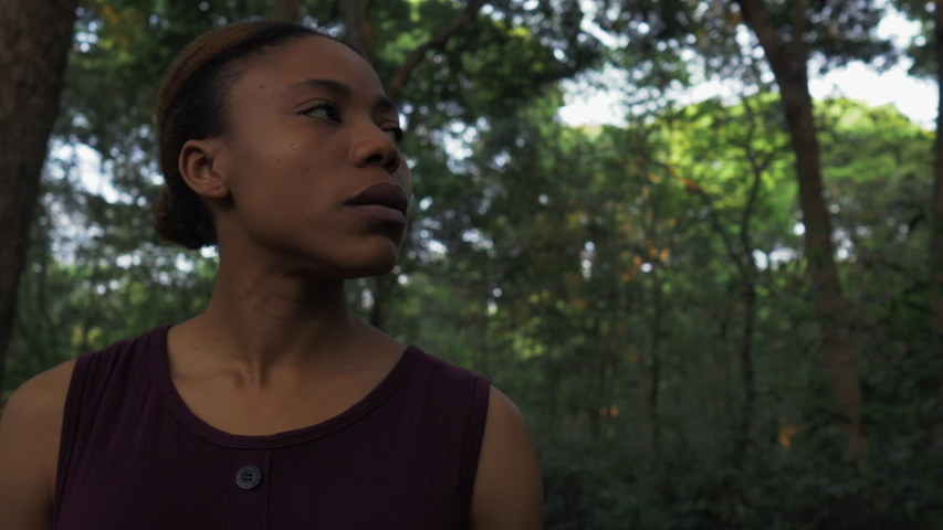 Low angle view One Young Black serious woman looking at jungle with sad face Close up of Young African woman looking around in the dark woods outdoor
