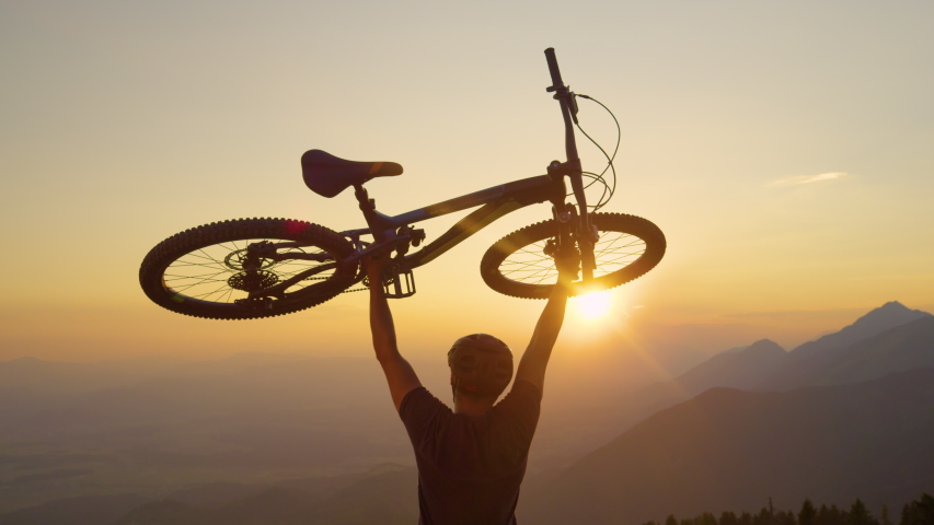 SLOW MOTION, SUN FLARE, CLOSE UP: Happy man lifts his bicycle above his head at sunset after a mountain biking trip in the beautiful mountains. Cheerful tourist celebrates winning a mountain bike ride