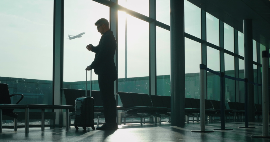 Slow motion of an young elegant businessman in a suit is walking with a suitcase in the international airport with a sunshine from the window. | Shutterstock HD Video #1029851108