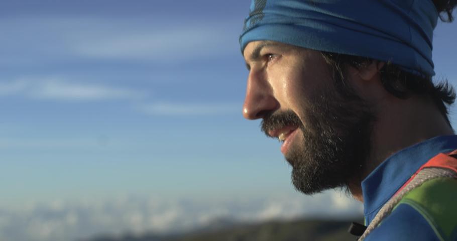Trail runner man running reaching mountain top peak goal looking horizon view.Portrait shot.Wild nature outdoors at sunrise or sunset backlit.Training activity,sport,effort,challenge,willpower concept | Shutterstock HD Video #1029853508