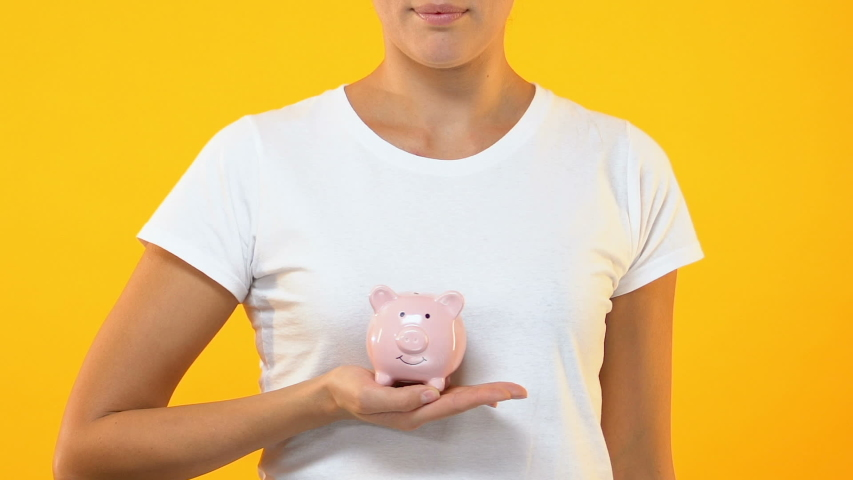 Smiling female holding piggy bank, family budget, savings for future investment