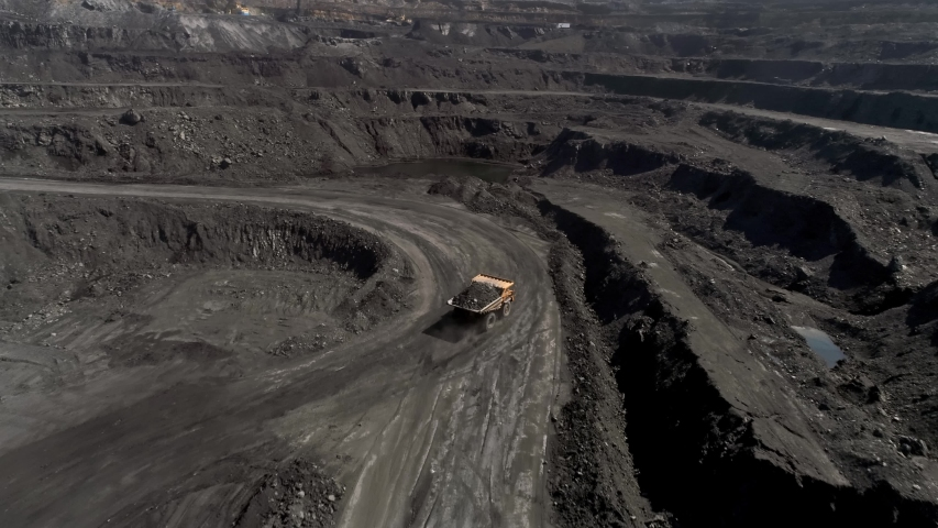 Panorama aerial view shot open pit mine coal mining, dumpers, quarrying extractive industry stripping work. Big Yellow Mining Trucks. View from drone at opencast mining with lots of machinery trucks | Shutterstock HD Video #1029938138