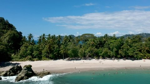 Aerial view of turquoise sea water and people walking in tropical rocky beach with jungle vegetation, waves reaching the sand in Manuel Antonio national park, Costa Rica. Pull out shot.