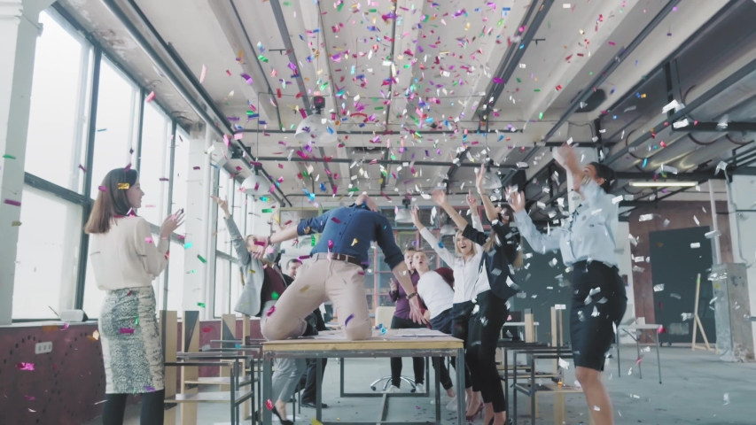 Manager start to dance on the table, sings into a megaphone, accelerates and slide on lap. Colleagues blow up flappers with confetti. Employees celebrate success. Corporate party business team