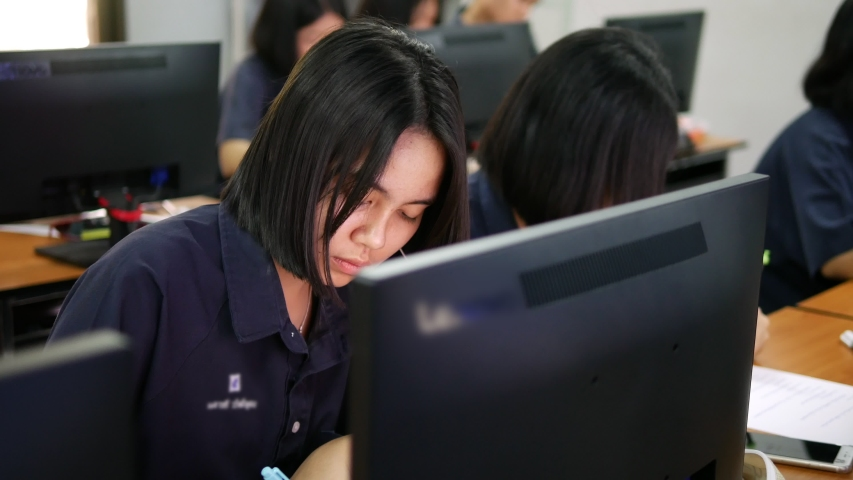 Asian high school female student is working by writing on paper and using searching from a desktop computer during computer study hours   Shutterstock HD Video #1029995408