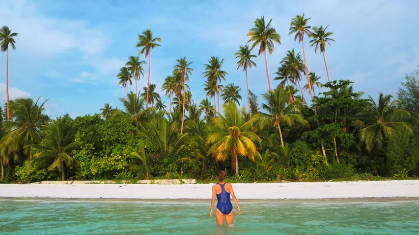 Slow motion: woman walking on white sand beach turquoise water tropical coastline Pasir Panjang Kei Islands Indonesia paradise travel destination sunset light | Shutterstock HD Video #1030045268