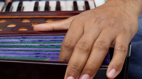 Closeup shot of a musician using his hand to pump the bellows to create the sound of the harmonium.