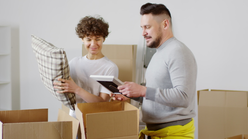 Panning medium shot of cheerful couple unpacking their belongings in their new home after house move, taking out cushions and framed family photos and rummaging through cardboard boxes   Shutterstock HD Video #1030096838