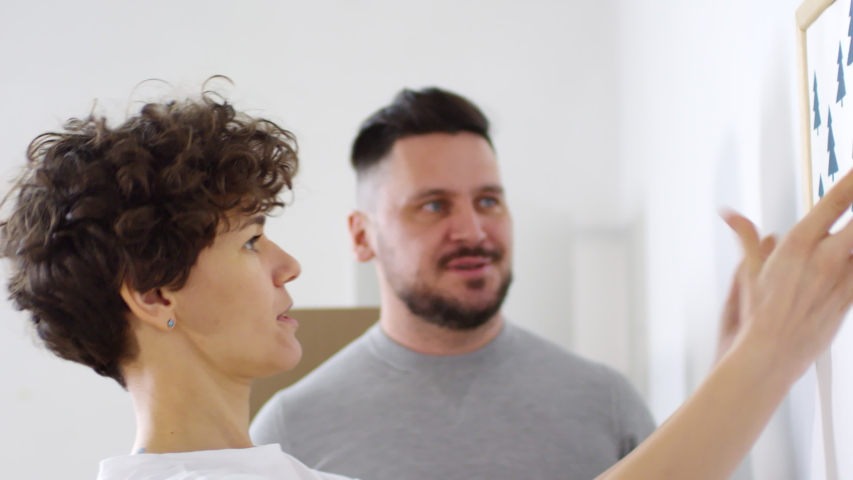 Close-up side shot of 40-something Caucasian man carefully hammering small nail into blank white wall, then curly woman putting up small framed picture, and both smiling with satisfaction   Shutterstock HD Video #1030099238