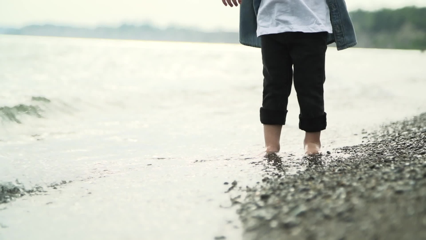 Camera shot of lower half of child in blue denim shirt standing barefoot in the water at the shore of a rocky beach. | Shutterstock HD Video #1030106228