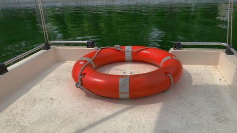 Orange, the lifeline lies on the edge of the boat, the boat floats on the green lake. Day, daylight hours.