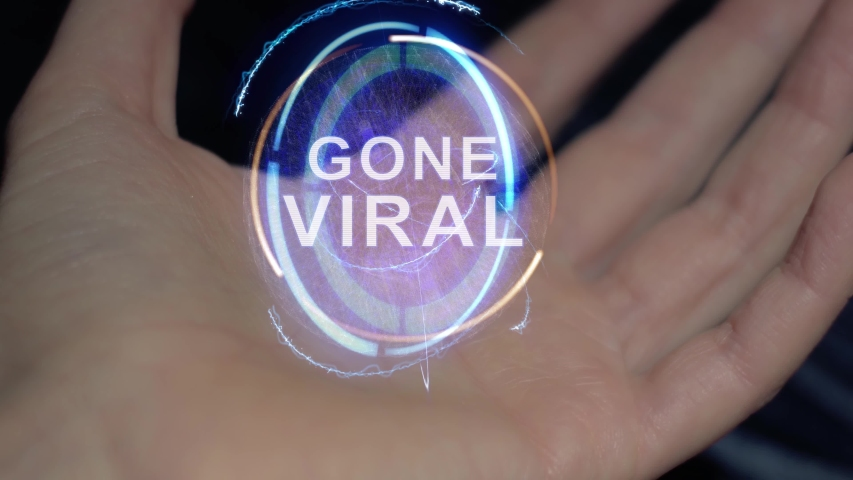 Gone Viral text in a round conceptual hologram on a female hand. Close-up of a hand on a black background with future holographic technology | Shutterstock HD Video #1030156808