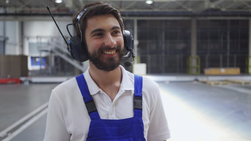 Factory worker talking through headphones and checking product quantities in warehouse | Shutterstock HD Video #1030246988